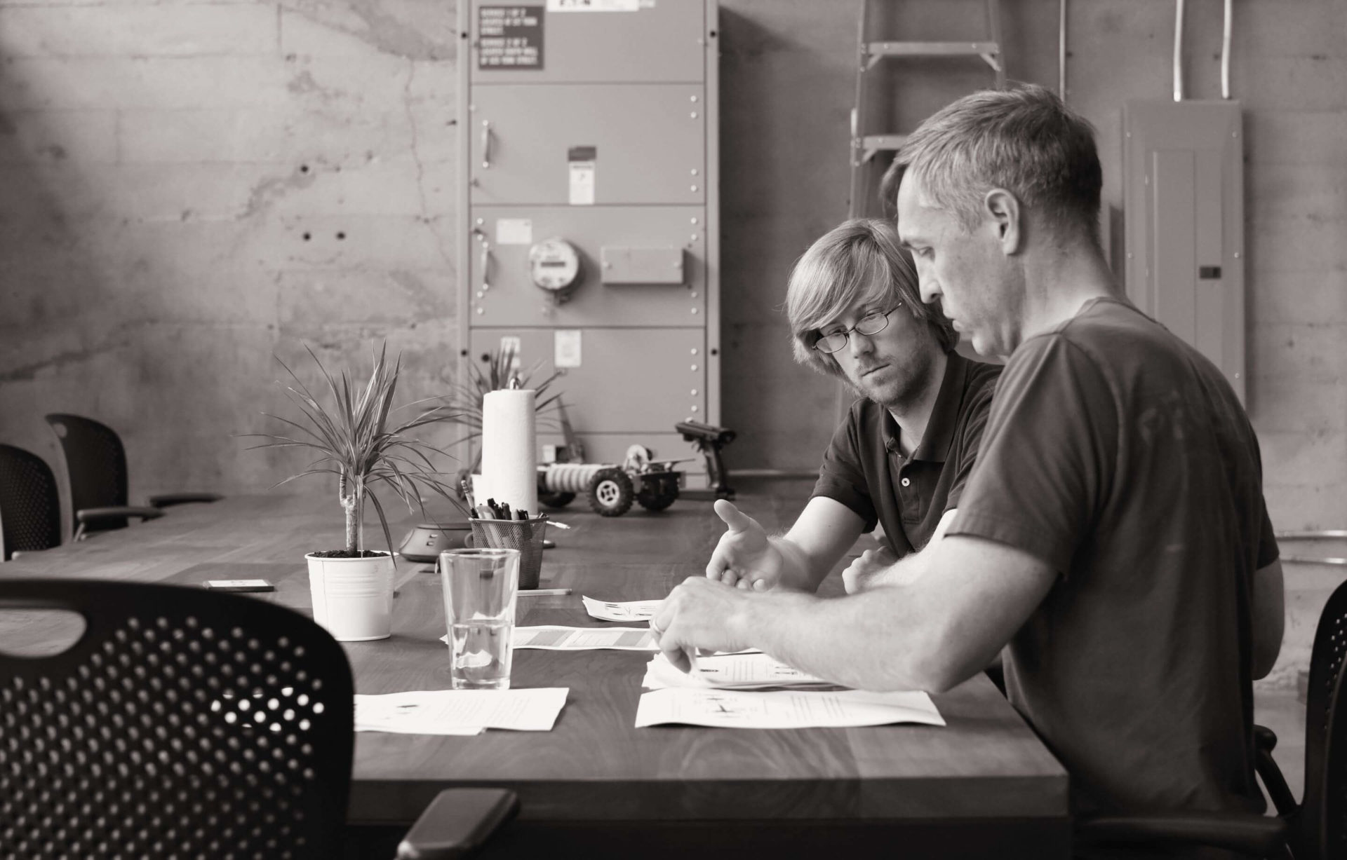 Two Cooper Perkins engineers sitting at a table discussing a project