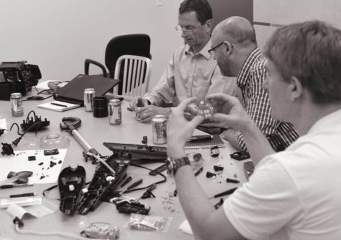 Three Cooper Perkins engineers sitting around a table inspecting various components of a project